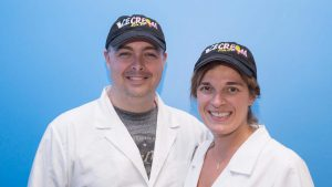 Sean and Yvonne, owners of Ice-Cream Lab, pose in their white coats and baseball caps.