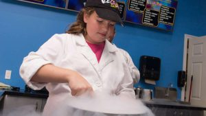 Young girl, Maya, whipping up an ice-cream concoction in a vat chilled by liquid nitrogen.