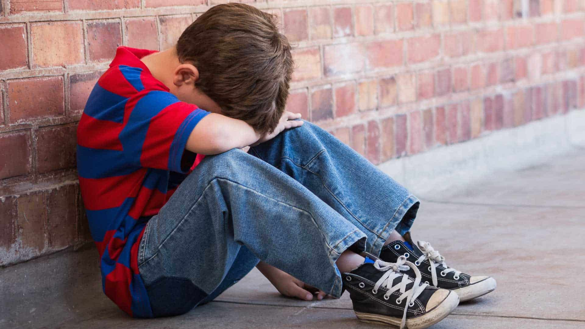 A young boy wearing jeans, sneakers and striped red and blue t-shirt is sitting on the floor next to the brick wall. He put his head on his forearm like he doesn't want to see anything
