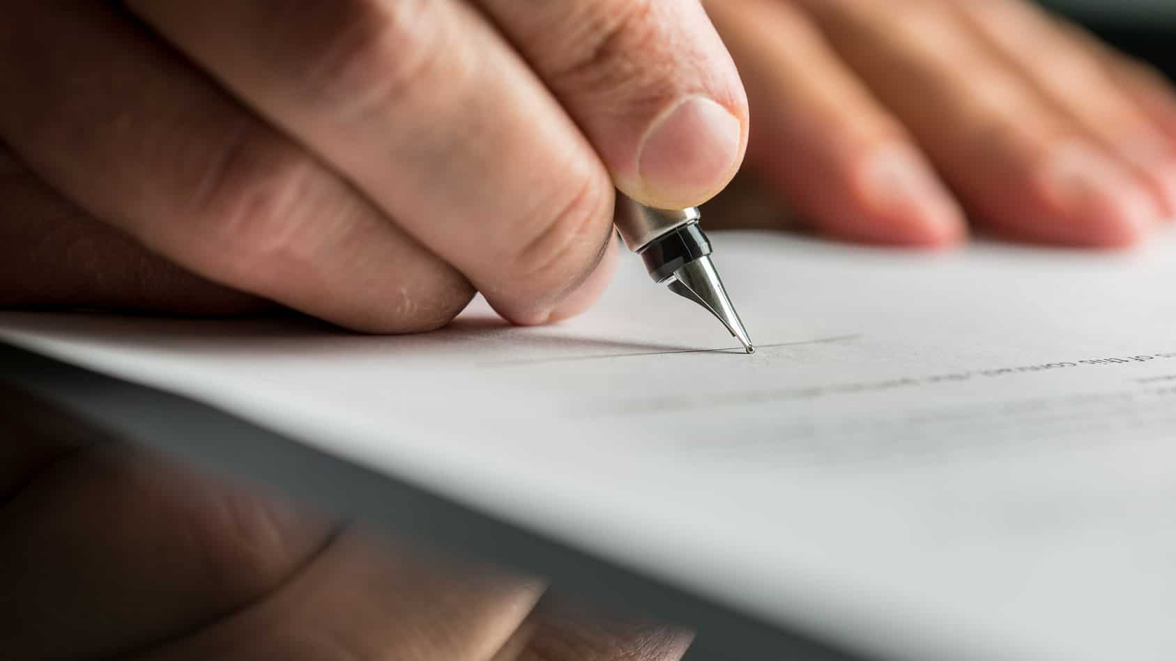 Closeup of male hand about to sign a paper with a fountain pen.