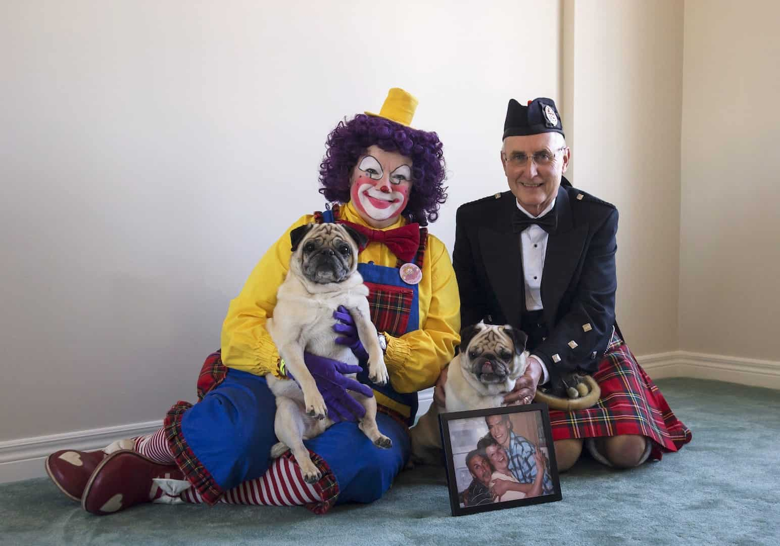 The woman dressed as a clown in yellow shirt and blue overalls, and the man in the scottish suit consist of red skirt, black jacket and a hat, are sitting together on their knees on the floor , each holds a pug-dog; a picture of their family stays in front of them.