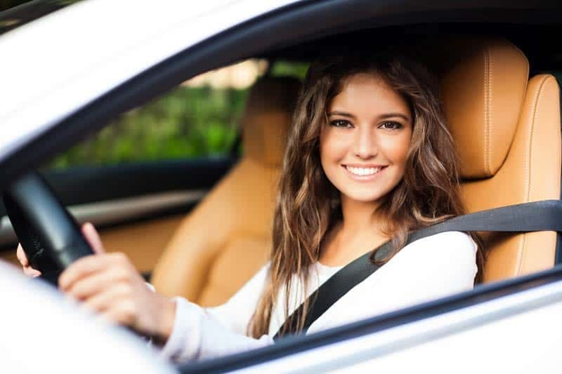 The young girl is sitting at the driving wheel of the car and holding the driving wheel. The seat belt is fastened. The girl has long brown hair and is wearing white sweater. The car seats are made of camel colored leather.