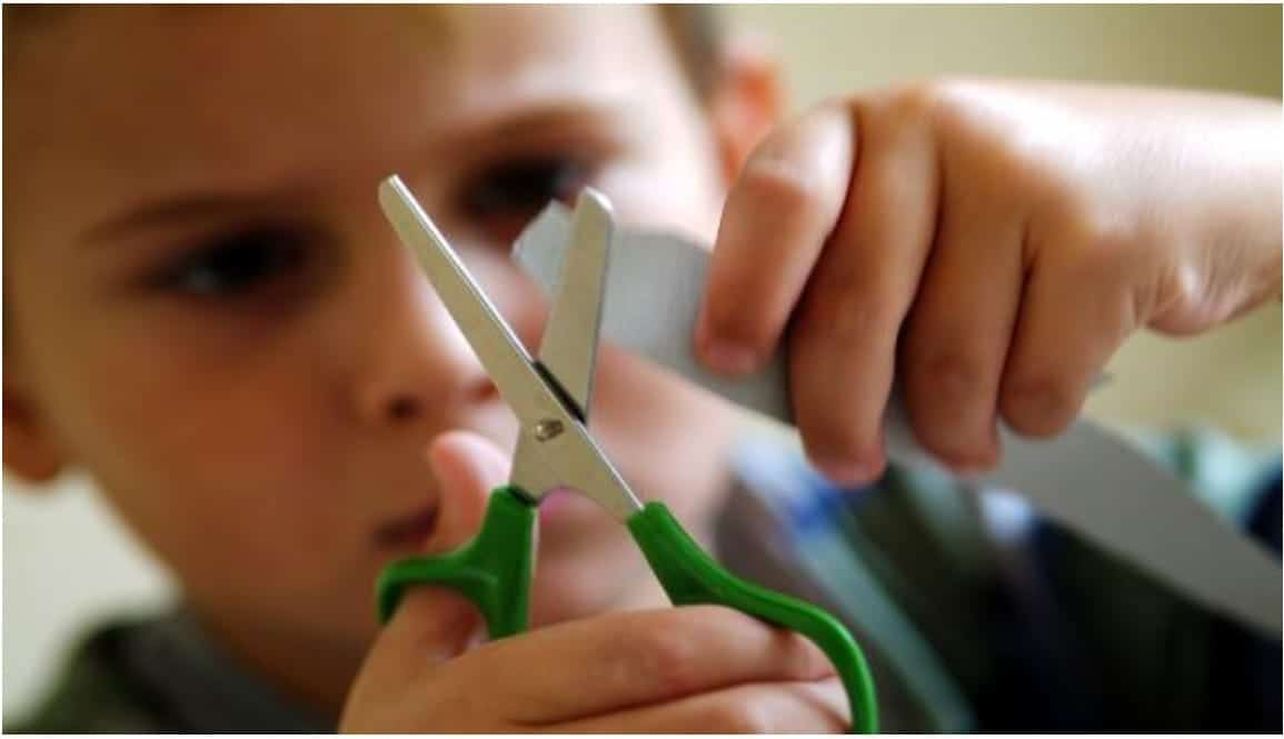 A face and hands of a young kid, which is holding small scissors with green handle and trying to cut a small piece of paper