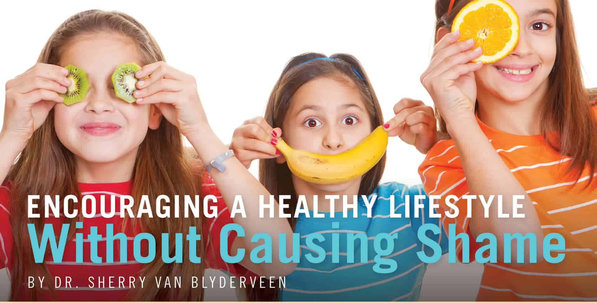 Portray of three young girls with long brown hair. The one in a red shirt covers her eyes with 2 slices of kiwi, the one in blue shirt covers her lips with banana, the tall girl in orange shirt covers her left eye with a round slice of an orange